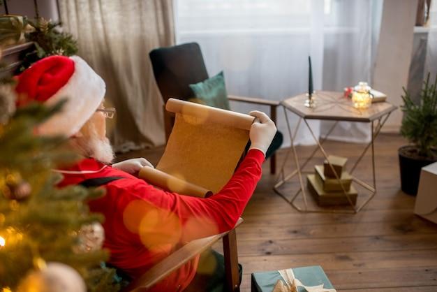 Papai noel em casa lendo uma carta