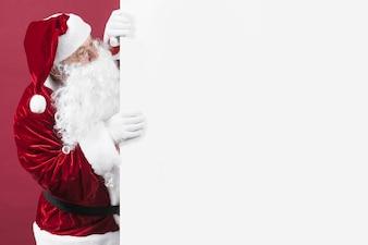 Papai Noel em copos, olhando para fora da parede branca