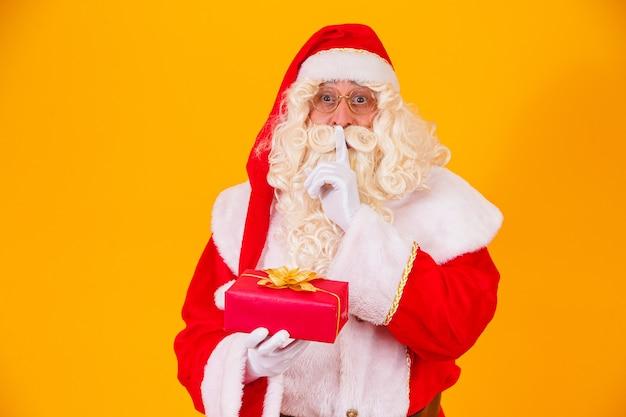 Papai noel em fundo amarelo segurando um presente nas mãos e fazendo um sinal de silêncio com a outra mão. surpresa do papai noel