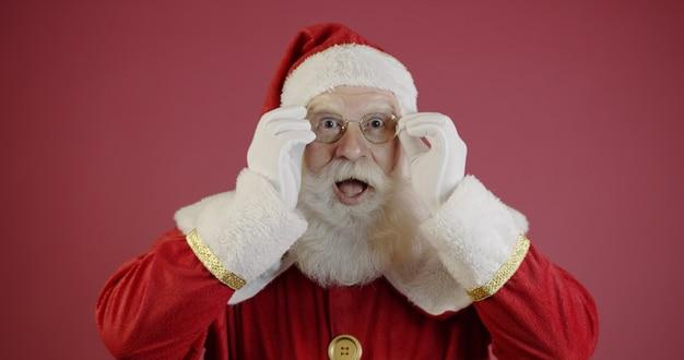 Papai noel em óculos está olhando para a câmera e sorrindo, sobre fundo vermelho