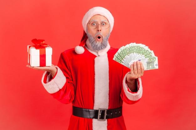 Papai noel em pé com a boca aberta e olhar animado, segurando uma caixa de presente e um leque de dinheiro.