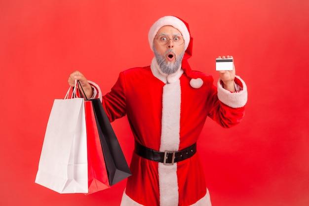Papai noel em pé com cartão de crédito e pacotes, compras, cartão ilimitado.