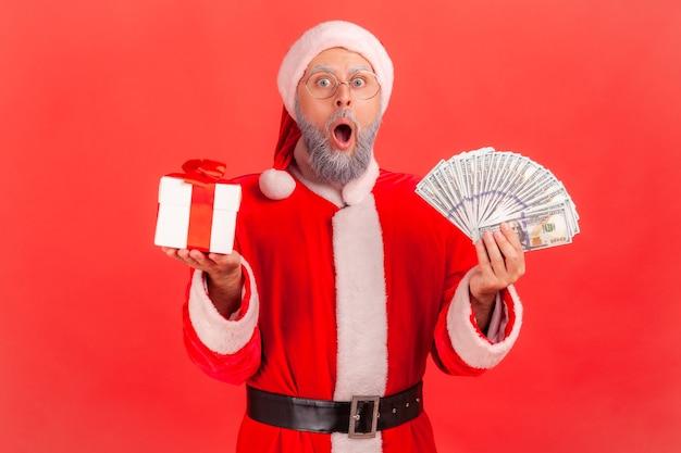 Papai noel em pé com leque de dólares e caixa de presente com presente de natal.