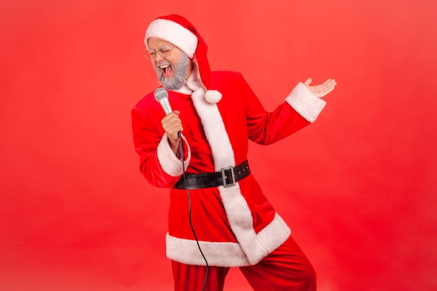 Papai noel em pé com o microfone nas mãos, cantando canções, celebrando o natal.