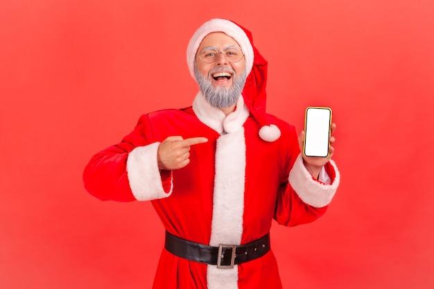 Papai noel em pé com o telefone inteligente nas mãos, apontando para uma tela em branco com o dedo indicador.