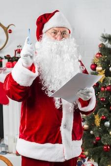 Papai noel em pé com papel perto de árvore de natal decorada