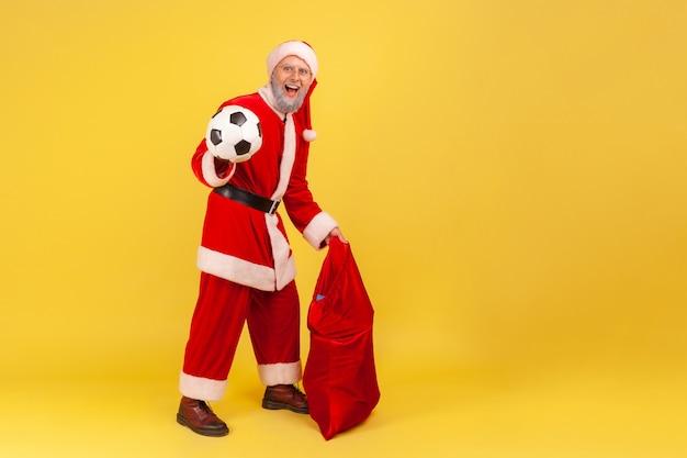 Papai noel em pé com uma bola de futebol e uma grande bolsa vermelha com presentes de natal.