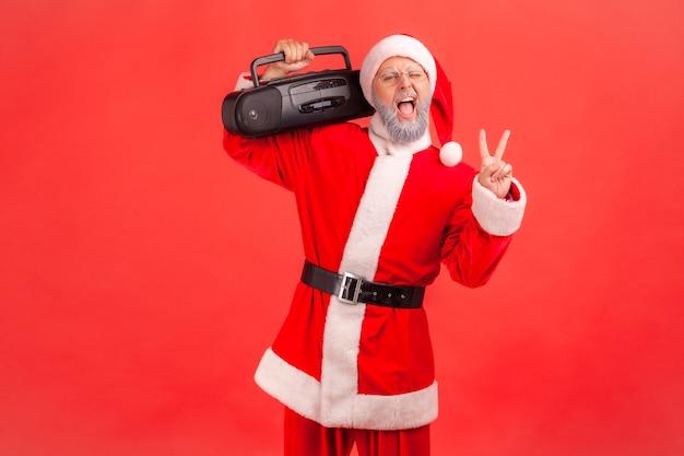Papai noel em pé e segurando o gravador mostrando o sinal de v, celebrando a festa de natal.