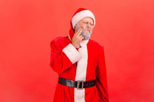 Papai noel em pé e tocando sua bochecha, sofrendo de uma terrível dor de dente.