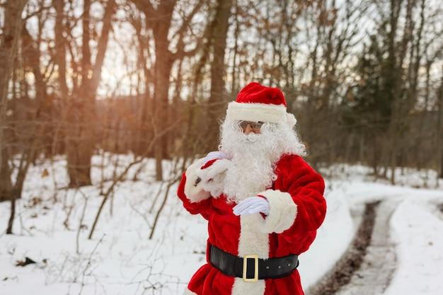 Papai noel em pé perto de uma árvore da floresta segurando uma sacola vermelha presentes para as crianças no natal perto da neve branca