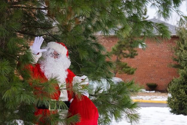 Papai noel em pé perto de uma árvore de natal segurando uma sacola vermelha com presentes para as crianças no natal perto da neve branca