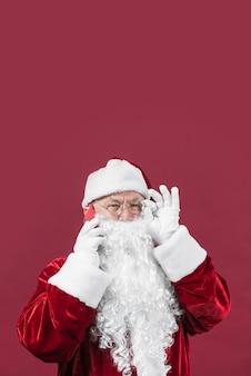 Papai noel em roupas vermelhas, falando por telefone