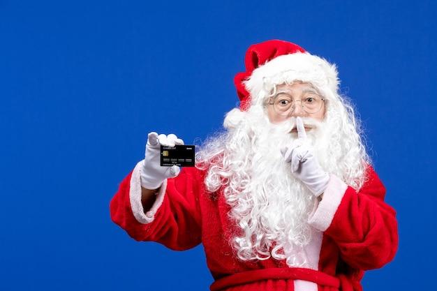 Papai noel em um terno vermelho segurando um cartão preto no feriado azul e apresentando a cor do natal.