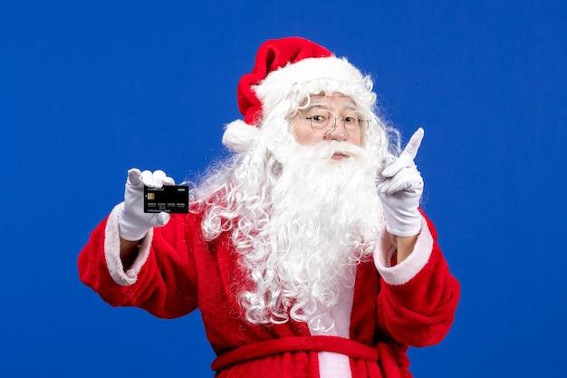 Papai noel em um terno vermelho segurando um cartão preto no feriado azul.