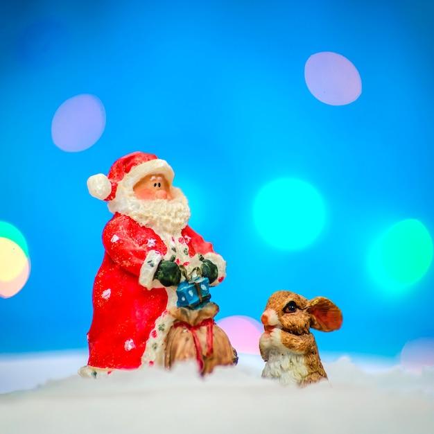 Papai noel em uma roupa vermelha com um coelho na neve em um fundo azul com iluminação