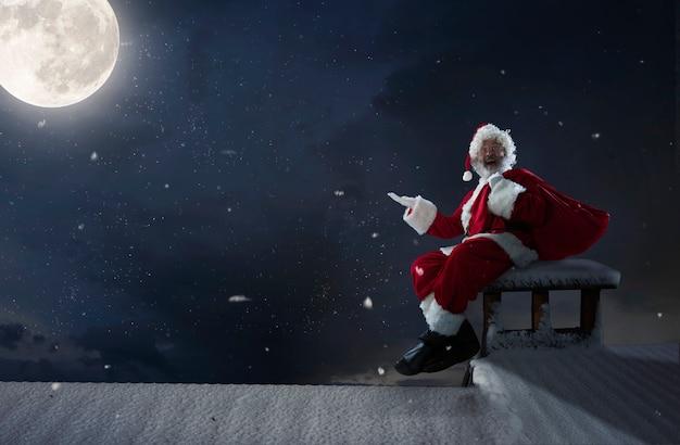 Papai noel emocional parabenizando com o ano novo de 2021 e o natal. homem em traje tradicional, sentado no telhado da casa com a lua cheia no fundo à meia-noite. inverno, feriados, vendas. copyspace.