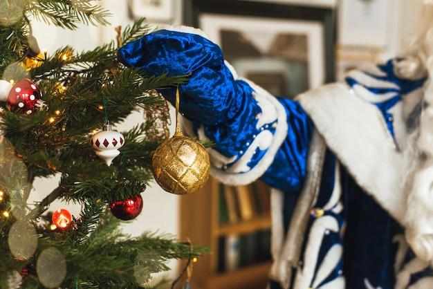 Papai noel engraçado decorando a árvore de natal