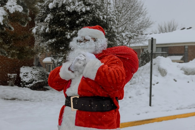 Papai noel entra em casa na véspera de natal carregando uma sacola de presentes
