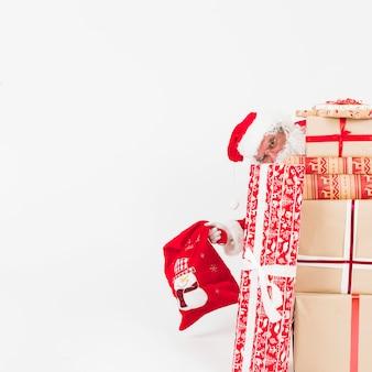 Papai noel espreitando de caixas de presentes