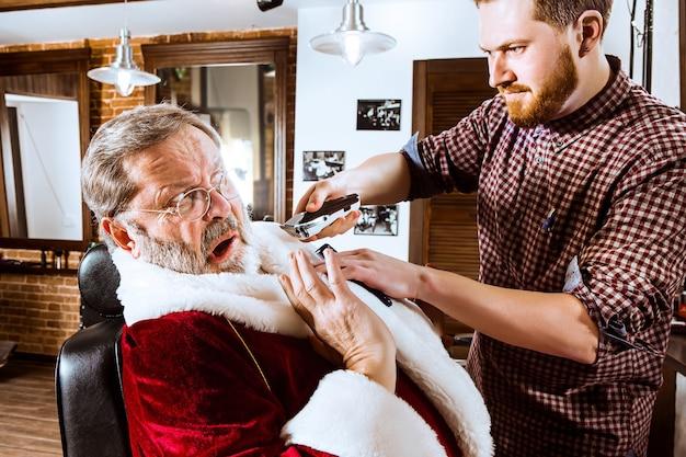 Papai noel fazendo a barba de seu barbeiro pessoal