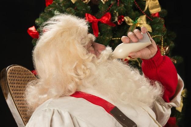 Papai noel feliz bebendo leite de garrafa de vidro contra a árvore de natal em casa