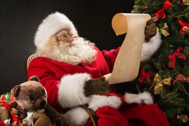 Papai noel feliz lendo carta de natal ou lista de desejos