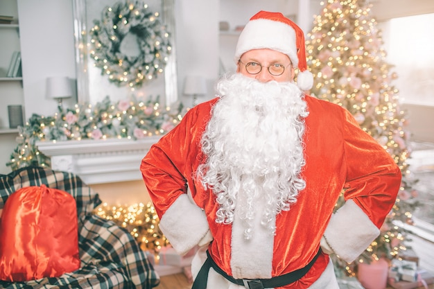 Papai noel fica em uma sala de estar com decoração de natal