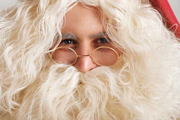 Papai noel fofo com olhos azuis acinzentados e óculos dourados, close-up retrato