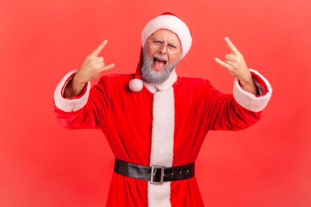 Papai noel gritando e mostrando placa de rock and roll, olhando para a câmera, comemorando o natal.