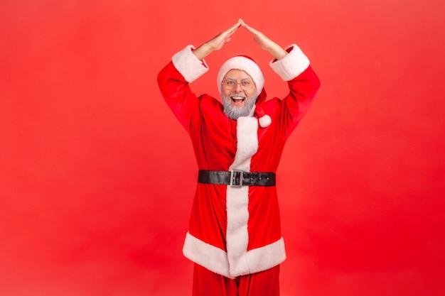 Papai noel levantando as mãos, mostrando o gesto do telhado, sonhando com a casa como presente de natal.