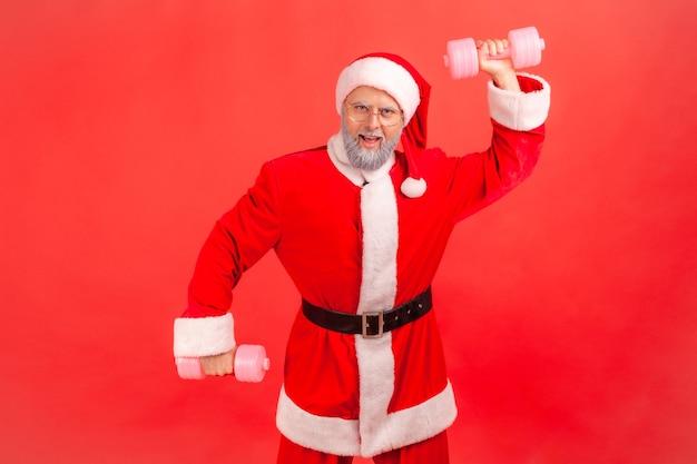 Papai noel levantou os braços com halteres rosa, olhando para a câmera, mostrando seu poder, parece orgulhoso.