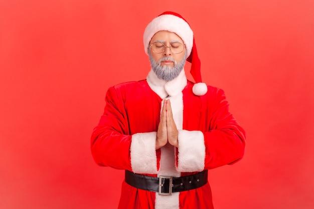 Papai noel mantendo o gesto namaste, meditando, técnica de respiração de exercícios de ioga reduz o estresse.