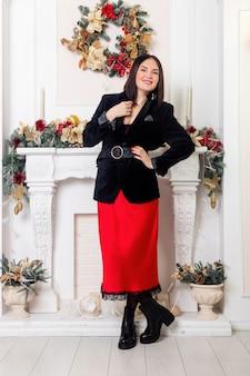 Papai noel. modelo de bela mulher sorridente. inventar. senhora elegante de saia vermelha e jaqueta preta sobre fundo de luzes de árvore de natal. feliz ano novo.