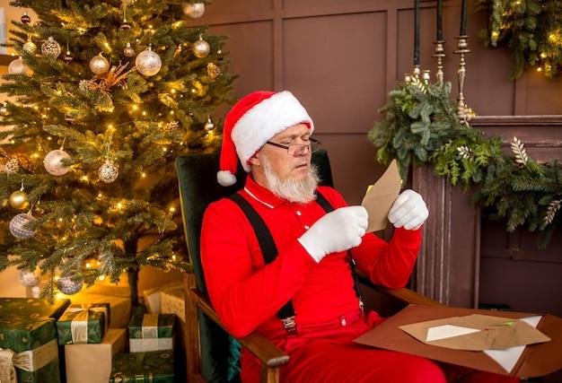 Papai noel moderno e luxuoso em casa lendo uma carta Foto Premium