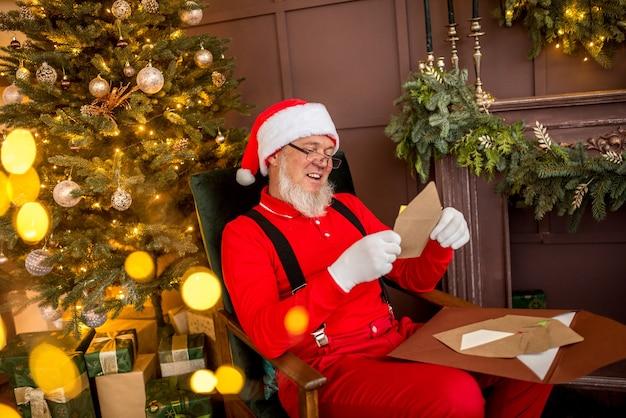 Papai noel moderno e luxuoso em casa lendo uma carta