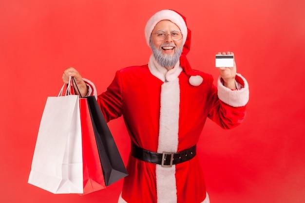 Papai noel mostrando para a câmera o cartão de crédito e sacolas de compras, grande reembolso, cartão ilimitado.