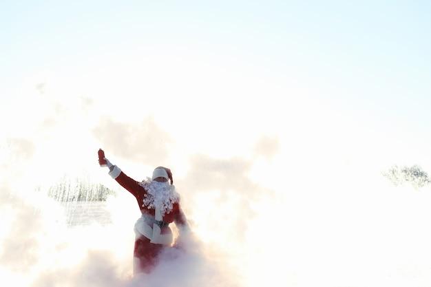 Papai noel no campo de inverno. névoa mágica de santa caminhando ao longo do campo. papai noel na véspera de natal está carregando presentes para as crianças em uma sacola vermelha