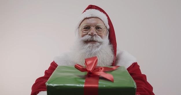 Papai noel oferecendo um presente para a câmera. recebendo presentes de natal. festas de ano novo.