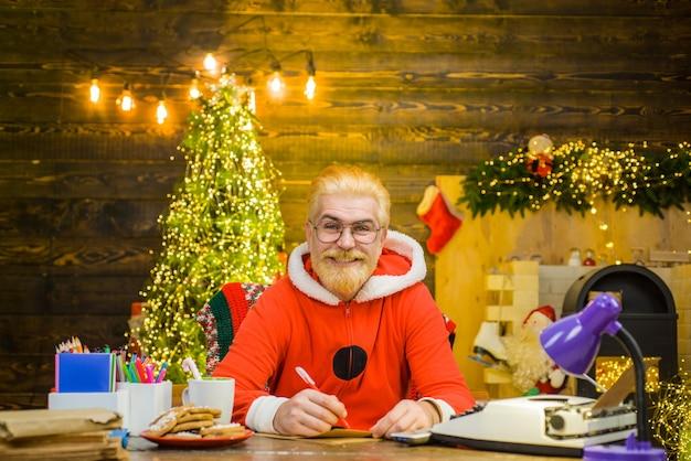 Papai noel, papai noel, senta-se à mesa, fundo de ano novo, decorações de natal, sorrindo, papai noel