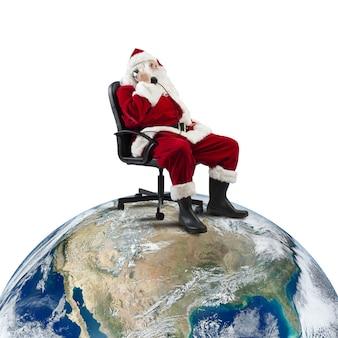 Papai noel recebe pedidos por telefone sentado em uma cadeira em um grande mundo