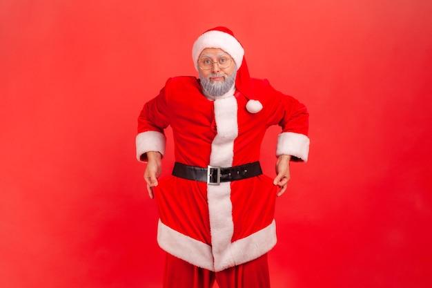 Papai noel revelando bolsos vazios, gesticulando que não tenho dinheiro antes das férias de natal.