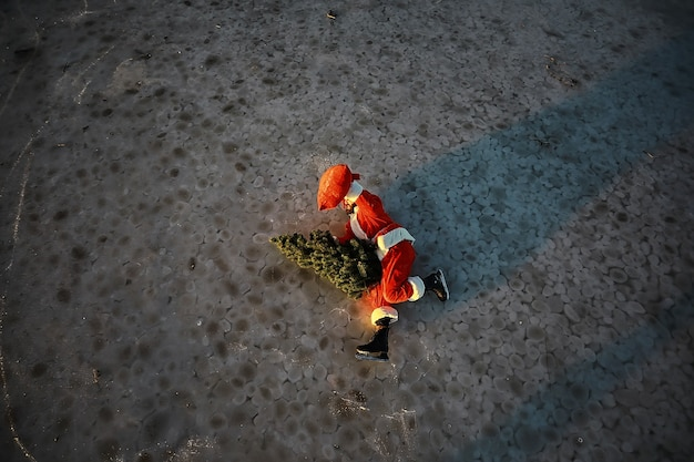 Papai noel se apressa para cumprir o ano novo com presentes e árvore de natal. papai noel de patins de gelo vai para o natal.