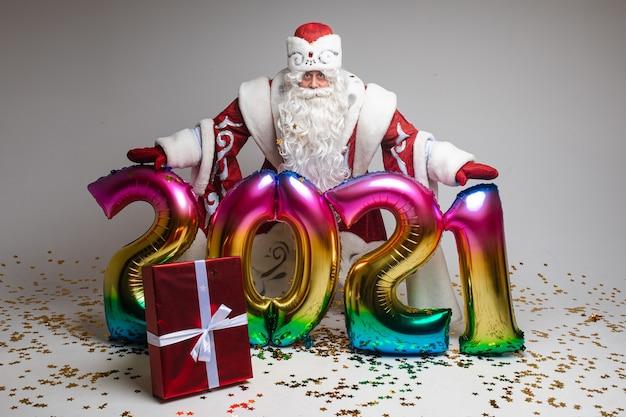 Papai noel segurando 2021 balões de ar coloridos.