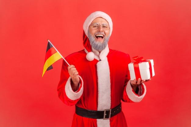 Papai noel segurando a bandeira alemã e a caixa com o presente de natal.