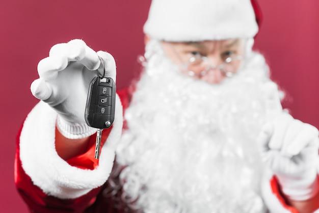 Papai noel segurando a chave do carro na mão
