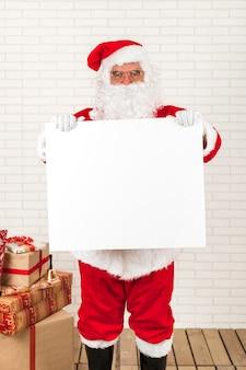 Papai noel segurando cartaz branco em branco