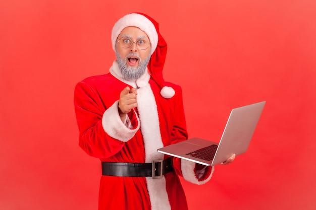 Papai noel segurando laptop nas mãos e apontando para a câmera com olhos grandes e espanto.