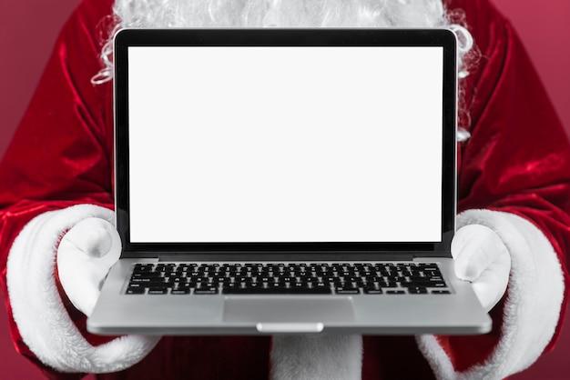 Papai noel segurando laptop nas mãos
