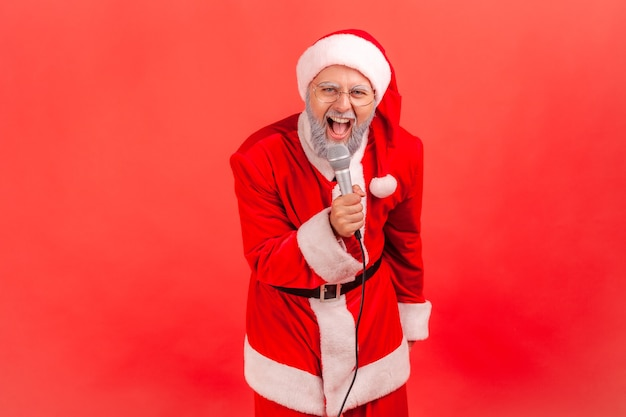 Papai noel segurando o microfone nas mãos, cantando na festa de natal no karaokê.