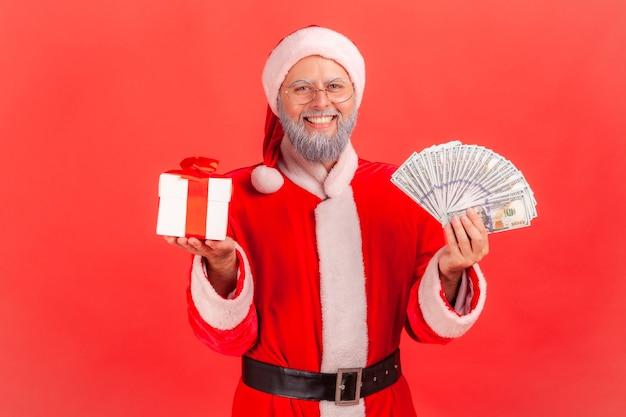Papai noel segurando um leque de dinheiro e embrulhado uma caixa de presente, olhando para a câmera com um sorriso.